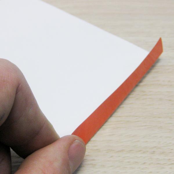 Ein leicht abgezogenes Etikett von Schlegel Etiketten mit einer roten Abziehhilfe