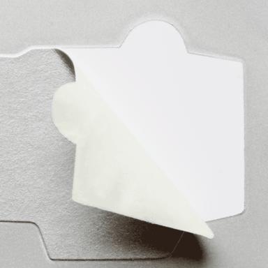Lackierschutz-Etiketten – Ein graues, halb abgezogenes Lackierschutzetikett mit spezifischen Formen