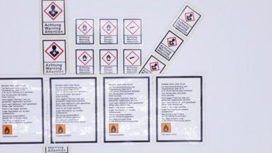 Mehrere Gefahrgutetiketten in auffälligen Farben mit aufgedruckten Warnhinweisen und Symbolen