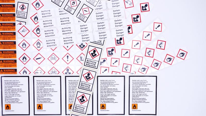 Mehrere Gefahrgutetiketten in auffälligen Farben mit aufgedruckten Warnhinweisen
