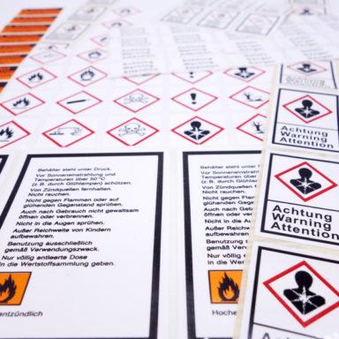 Mehrere Gefahrgutetiketten mit aufgedruckten Warnhinweisen in der Nahansicht