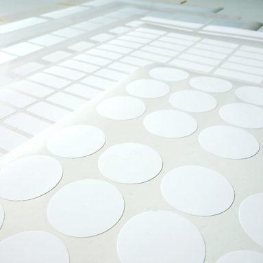 Mehrere Bogenetiketten-Produkte von Schlegel Etiketten verschiedenster Formate liegen übereinander