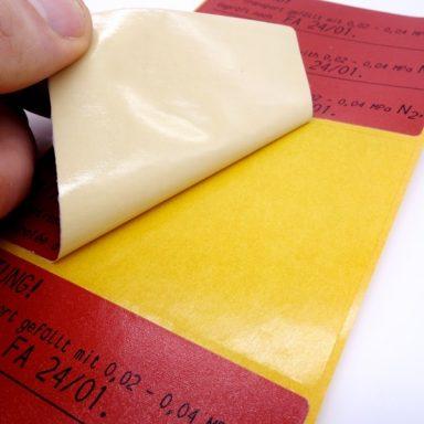 Ein stark haftendes Etikett wird für eine ölige Oberfläche abgezogen